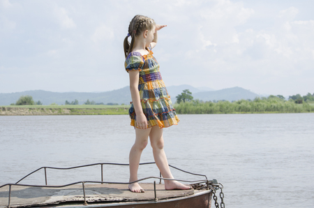 A girl stands on a boat and looking into the distance. Rural landscape.
