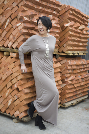 Beautiful Korean girl standing next to the new bricks. A brick factory. Stock Photo