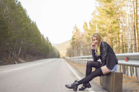 torn stockings: Beautiful young girl hitchhiking in the United States and Canada.
