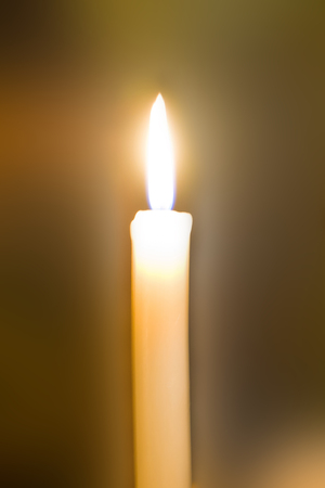 heal new year: A lone candle lights the dark room. The candle burns with a bright light.