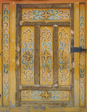 mongols: Old wooden door into the tent. The door is painted with a traditional pattern