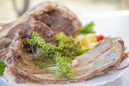 Boiled mutton laid out on a platter with fresh vegetables.