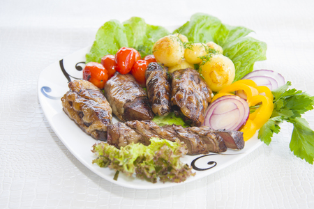 The liver of a sheep fried in a shirt on charcoal with vegetables. Stock Photo