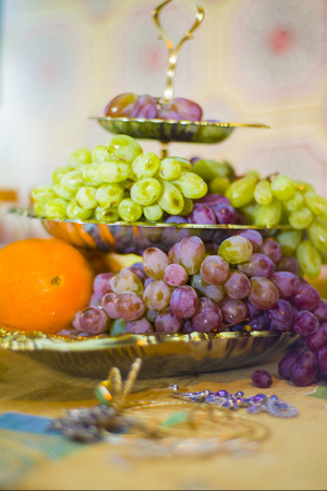 Fruits lie on a three-tiered fruit plate. Item of the Eastern interior.