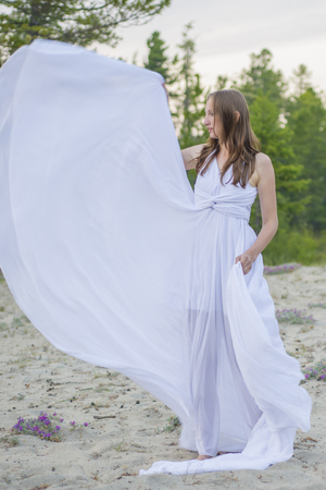 Beautiful girl dancing on the beach, her dress fluttering in the wind.