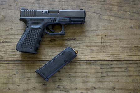 amendment: 9mm Pistol handgun on a wooden table with the magazine