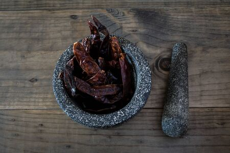 spicey: Dried Chili Peppers in  Stone Mortar with Pestle Stock Photo