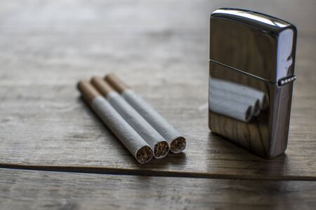 habbit: Vintage cigarettes with reflective silver lighter Stock Photo