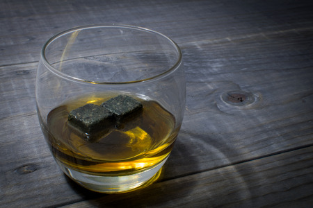 whiskey on the rocks: Whiskey with Whisky Rocks on a Wooden Table