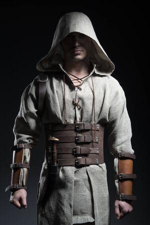 guerrero: hombre con una capa con un cuchillo sobre un fondo gris