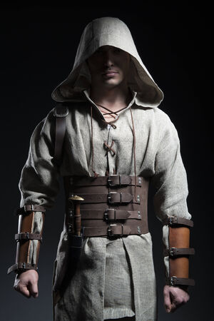 warrior: man in a cape with a knife on a gray background