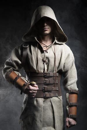 guerrero: hombre con una capa con un cuchillo en la mano sobre un fondo gris