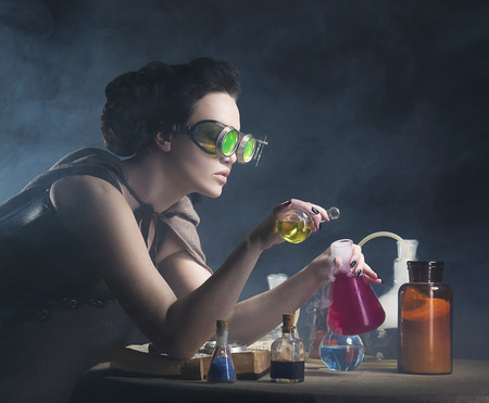 alchemist girl with test tubes in hand on a gray background Imagens