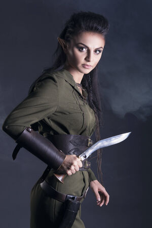 beautiful elf with a knife in his hand photo