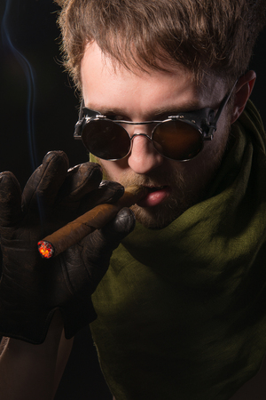 man in a green scarf with a cigar in his hand