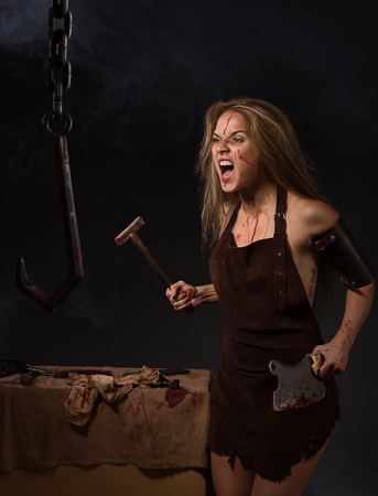 maniac: maniac woman with a knife in his hand on a gray background Stock Photo