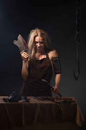 maniac woman with a knife in his hand on a gray background Imagens