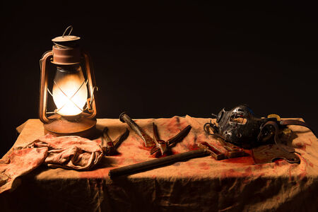 torture: lamp, knife and a mask on the table on a gray background