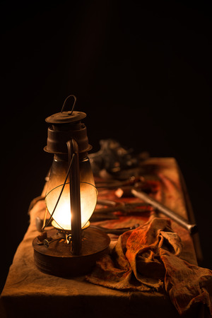 lamp, knife and a mask on the table on a gray background