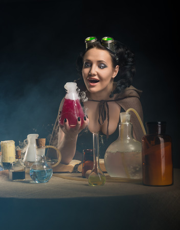 Alchemist girl with test tubes on gray background