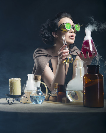 alchemist girl th test tubes in hand on a gray background Imagens