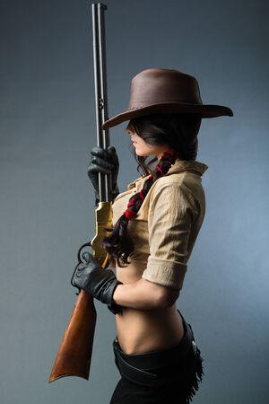 mujer con arma: vaquero chica con una pistola sobre un fondo gris Foto de archivo