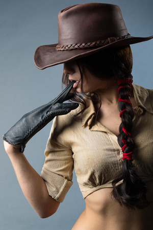 girl cowboy with a gun on a gray background Imagens