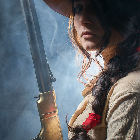 western clothing: girl cowboy with a gun on a gray background Stock Photo
