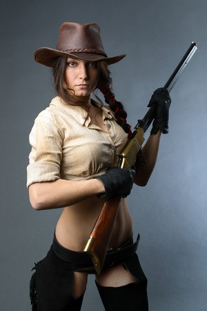 west country: Beautiful cowgirl with gun on gray background