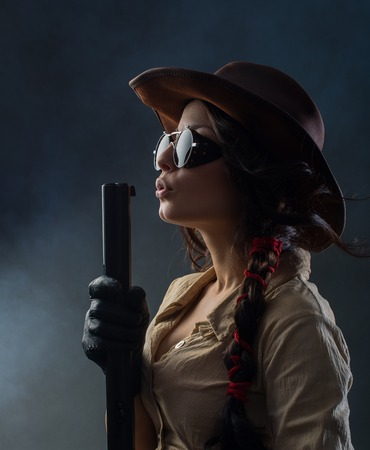 cowgirls: Hermosa vaquera con una pistola sobre fondo gris