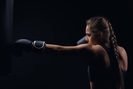 pushes: young girl in boxing gloves pushes the bag on a black background