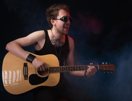 handsome musician playing guitar on black background Imagens