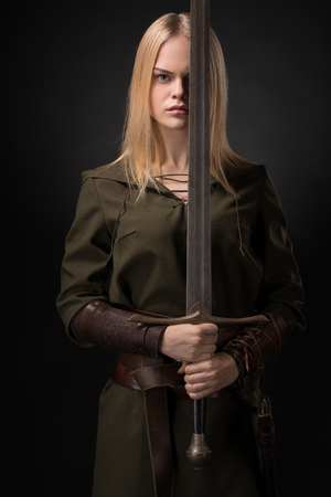 Woman warrior with sword in hand on gray background Imagens