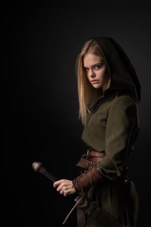灰色の背景に手に剣を持つ女性戦士