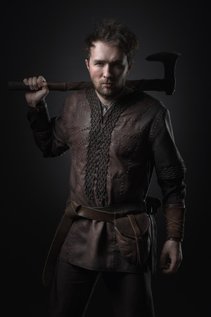 Man viking with an ax against a black background