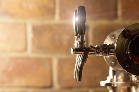 백그라운드에서 벽돌 맥주 탭 기계의 필드 샷의 얕은 깊이.