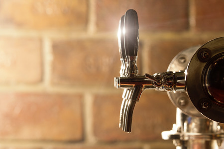 Shallow depth of field shot of beer tap machine with bricks in the background. Stock Photo