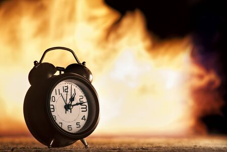 Dramatic picture of alarm clock with fire in the background