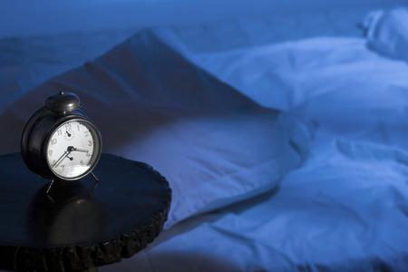 despertar: Reloj despertador con cama vacía y efecto-moon luz.
