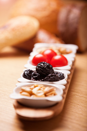 Dried prunes, nuts and tomatoes with bread in the background