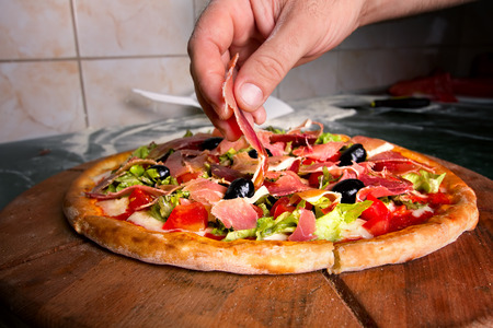 Hand of cook is preparing pizza. Final touch Banco de Imagens