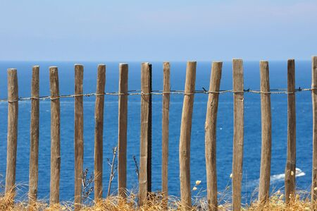Wooden fence in front of a blue sea