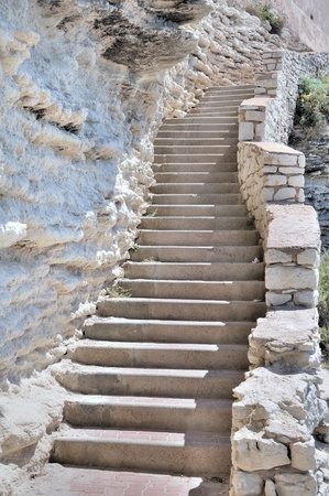 Many steps of a staircase along a limestone cliff Stock Photo