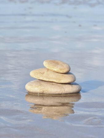 fullness: Pebbles and their reflection  stacked on the sea Stock Photo