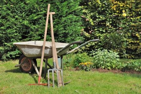 carretilla: carretilla antigua y herramientas de jardines
