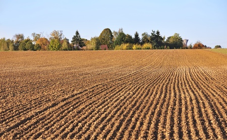 furrows: furrows in field heading straight to a small village on the horizon Stock Photo