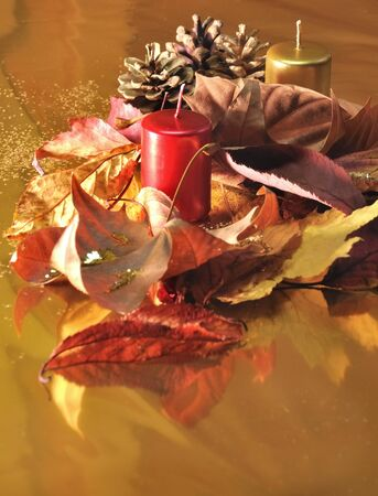 Red and golden candles  with leaves and pine cones on a golden background photo