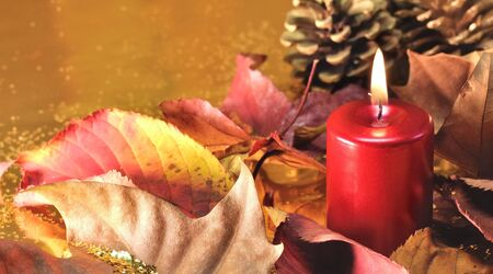 Red candles lit  with leaves and pine cones on a golden background Stock Photo - 11557874