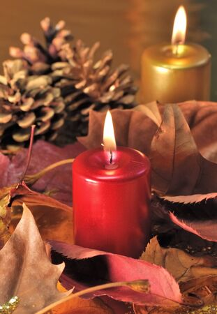 Red and golden candles lit  with leaves and pine cones on a golden background photo