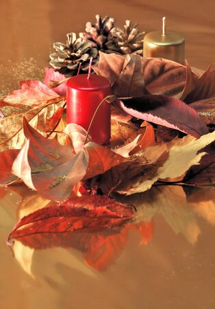 Red and golden candles  with leaves and pine cones on a golden background Stock Photo - 11557878